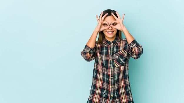 Jeune femme sur mur bleu excité en gardant le geste ok sur les yeux.