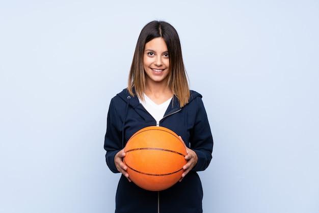 Jeune femme sur un mur bleu isolé avec ballon de basket