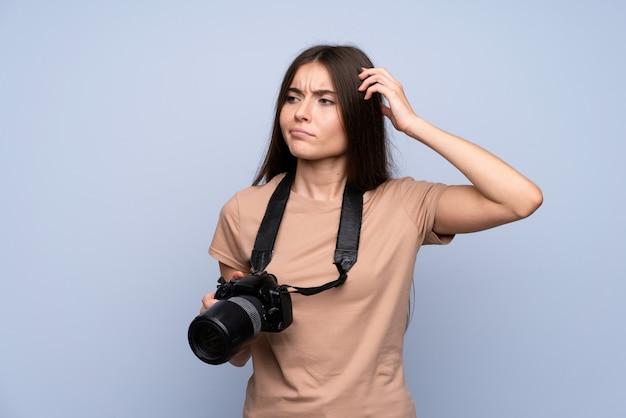 Jeune femme sur un mur bleu isolé avec une caméra professionnelle et pensant
