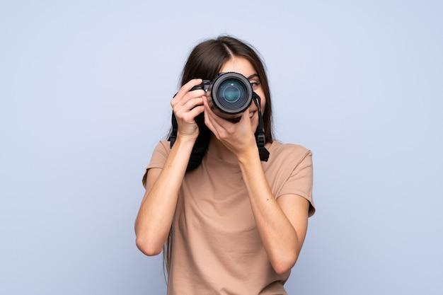 Jeune femme sur un mur bleu isolé avec une caméra professionnelle