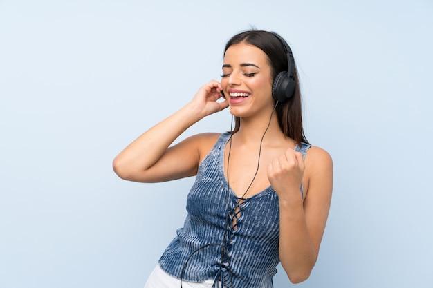 Jeune femme sur un mur bleu isolé, écouter de la musique avec des écouteurs