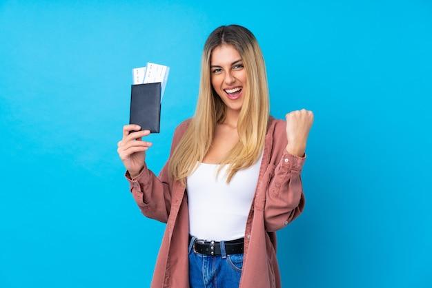 Jeune femme sur mur bleu isolé heureux en vacances avec passeport et billets d'avion