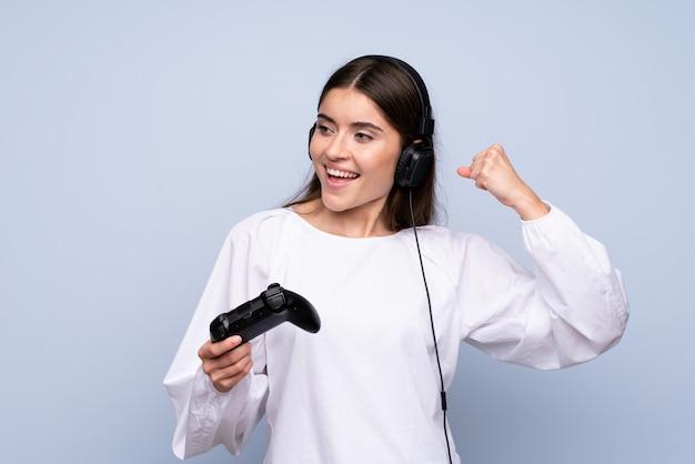 Jeune femme sur un mur bleu isolé jouant à des jeux vidéo