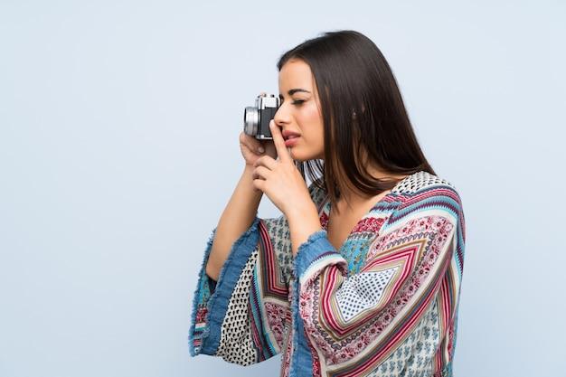 Jeune femme sur un mur bleu isolé, tenant une caméra