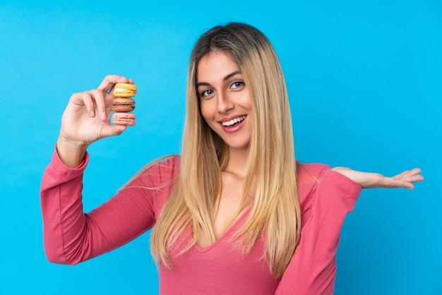 Jeune femme sur un mur bleu isolé tenant des macarons français colorés avec une expression choquée