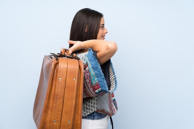 Jeune femme sur un mur bleu isolé, tenant une mallette vintage