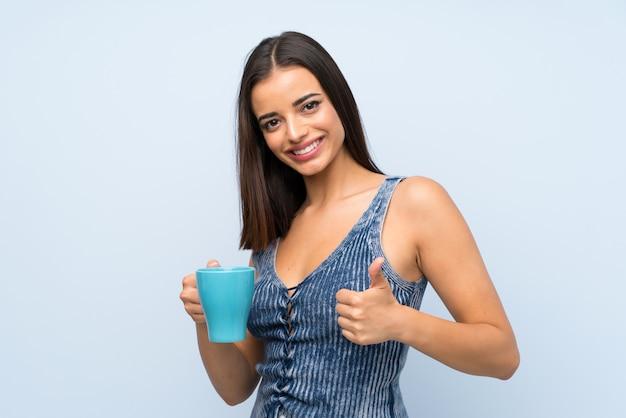 Jeune femme sur mur bleu isolé, tenant une tasse de café