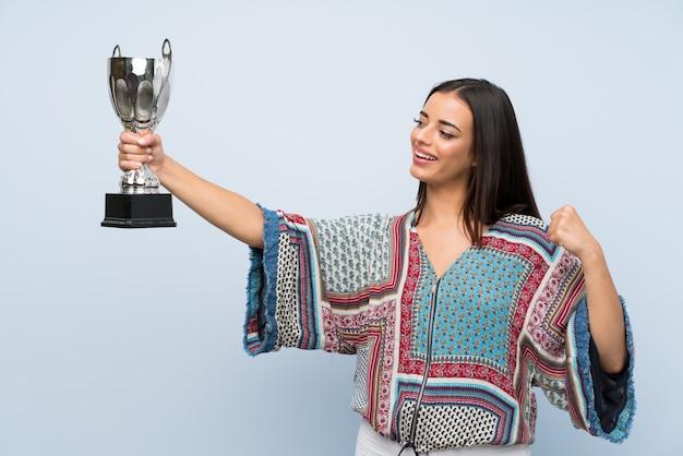 Jeune femme sur un mur bleu isolé, tenant un trophée