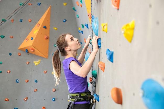 Jeune femme mur d'escalade en salle de sport