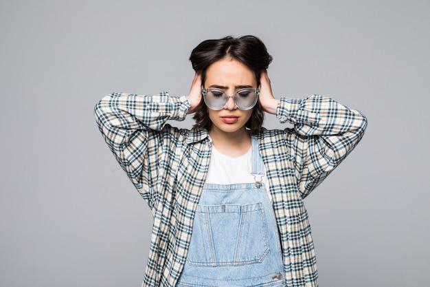 Jeune femme sur un mur gris portant des lunettes de soleil stressée avec la main sur la tête, choquée par la honte et le visage surpris, en colère et frustrée. peur et colère pour erreur.