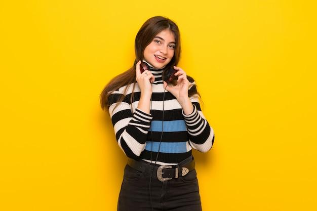 Jeune femme sur un mur jaune avec un casque