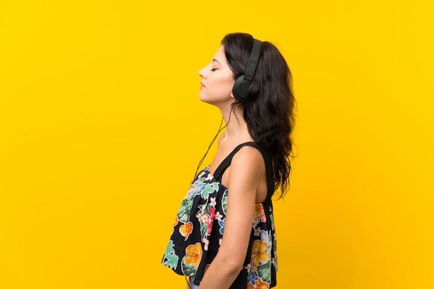 Jeune femme sur un mur jaune isolé, écouter de la musique avec des écouteurs
