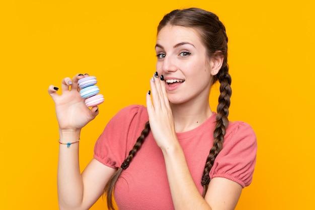 Jeune femme sur un mur jaune isolé tenant des macarons français colorés et chuchoter quelque chose