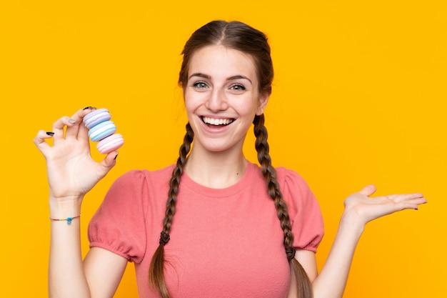 Jeune femme sur un mur jaune isolé tenant des macarons français colorés avec une expression choquée