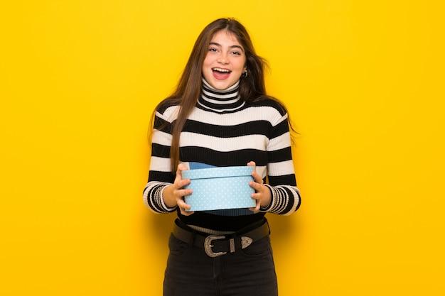 Jeune femme sur un mur jaune surprise parce qu'un cadeau lui a été offert
