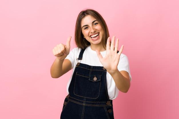 Jeune femme sur mur rose isolé comptant six avec les doigts