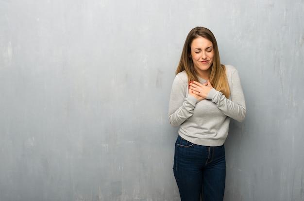 Jeune femme sur un mur texturé ayant une douleur au coeur