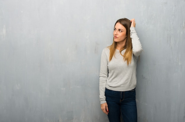 Jeune femme sur un mur texturé ayant des doutes tout en grattant la tête