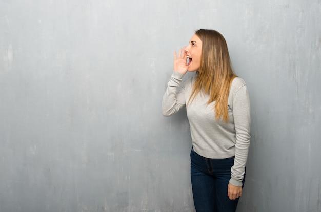 Jeune femme sur un mur texturé criant avec la bouche grande ouverte sur le côté