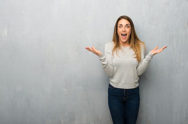 Jeune femme sur un mur texturé avec expression faciale surprise et choquée