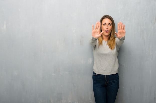 Jeune femme sur un mur texturé faisant un geste d'arrêt pour déçu par un avis