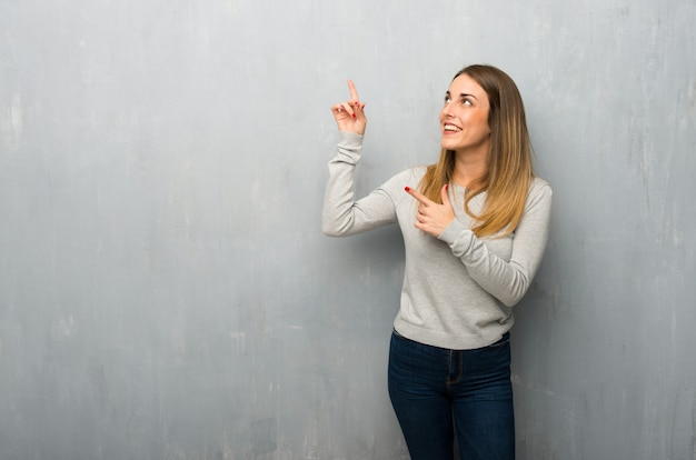 Jeune femme sur un mur texturé pointant avec l'index et levant