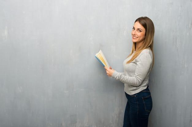 Jeune femme sur un mur texturé tenant un livre et lire