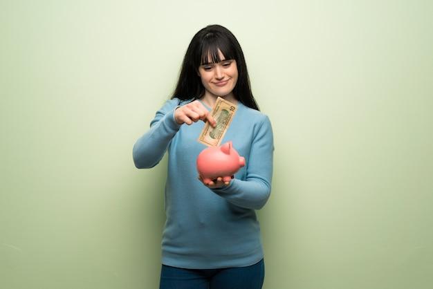 Jeune femme sur un mur végétal prenant une tirelire et heureuse parce qu'elle est pleine