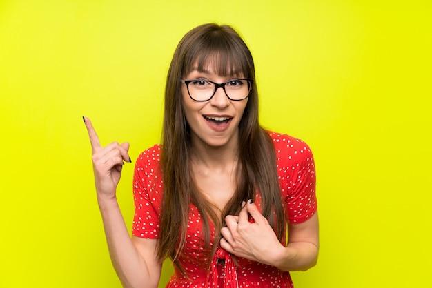 Jeune femme sur un mur vert avec une expression faciale surprise