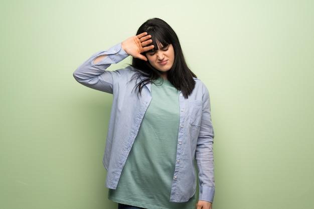 Jeune femme sur un mur vert avec une expression fatiguée et malade