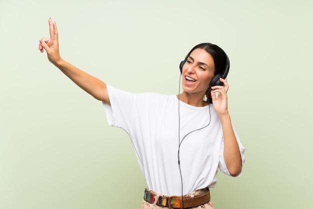Jeune femme sur un mur vert isolé, écouter de la musique avec des écouteurs