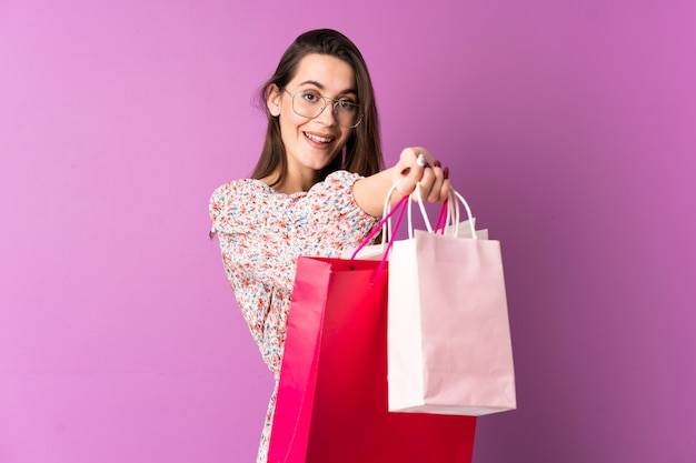 Jeune femme sur un mur violet isolé tenant des sacs à provisions et les donnant à quelqu'un