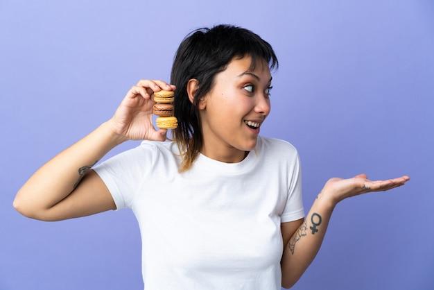 Jeune femme sur un mur violet tenant des macarons français colorés et avec une expression surprise