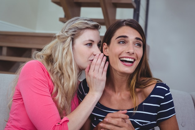Jeune femme murmurant un secret à son amie