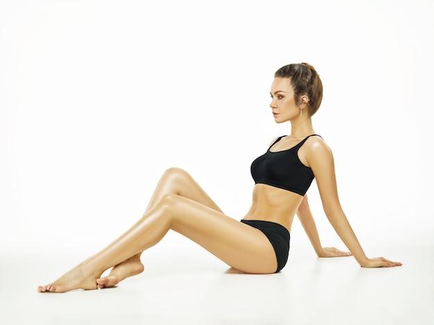 Jeune femme musclée ou athlète féminine posant au studio isolé sur fond blanc. fit modèle caucasien avec un corps parfait. fitness, sport, beauté, concept de peau fraîche.