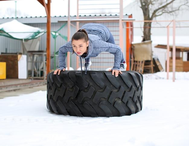 Jeune femme musclée formation sur pneu lourd, à l'extérieur