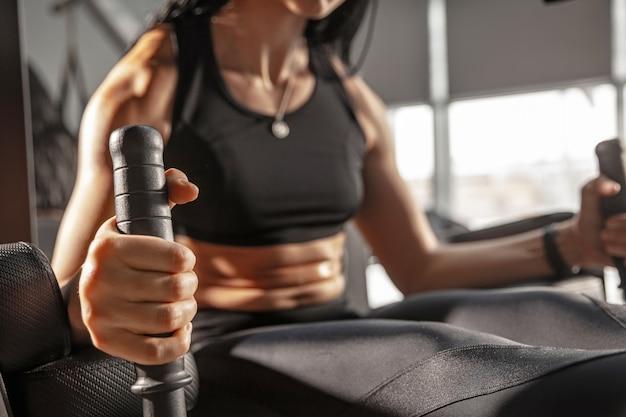Jeune femme musclée pratiquant dans une salle de sport avec équipement