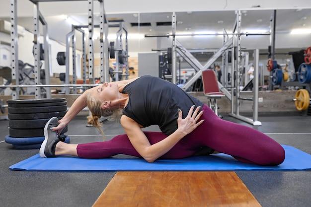 Jeune femme musculaire athlétique faisant des étirements