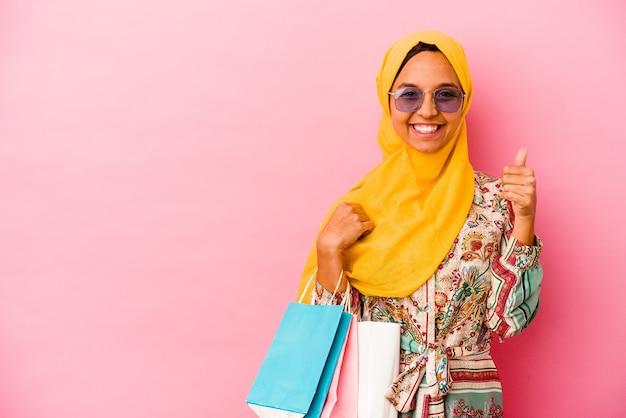 Jeune femme musulmane, acheter des vêtements isolés sur un mur rose souriant et levant le pouce vers le haut