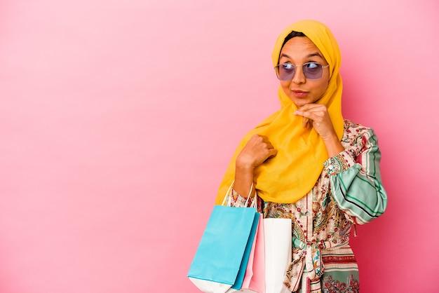 Jeune femme musulmane, acheter des vêtements sur le rose à la recherche de côté avec une expression douteuse et sceptique.