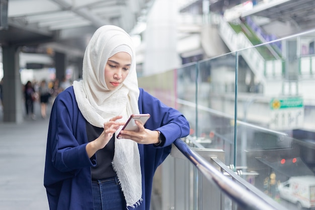 Jeune femme musulmane à l'aide de smartphone.