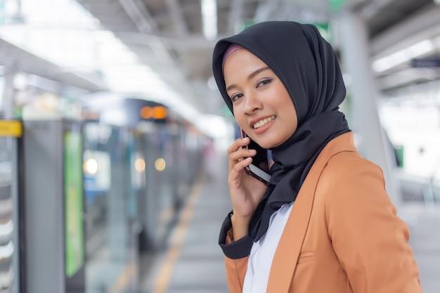 Jeune femme musulmane à l'aide de téléphone sur la station de skytrain.