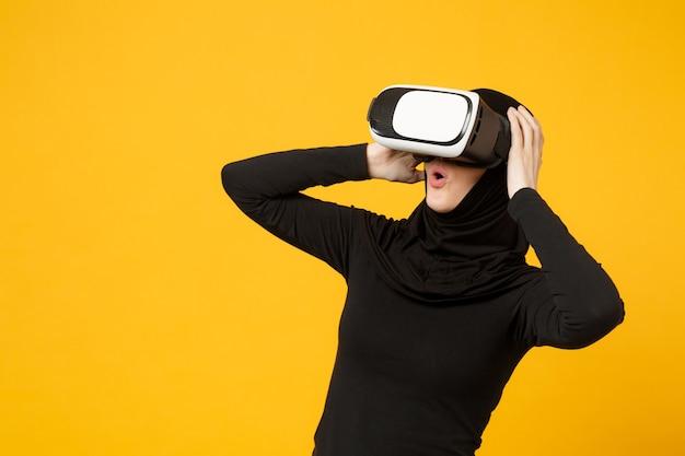 Jeune femme musulmane arabe en vêtements noirs hijab regardant dans un casque de réalité virtuelle vr isolée sur un portrait de mur jaune. concept de mode de vie religieux des gens.