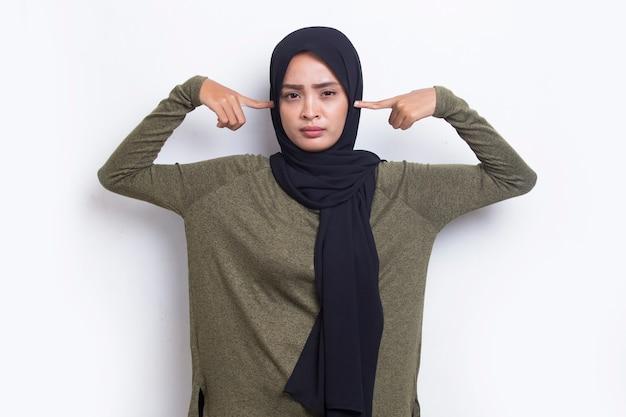 Jeune femme musulmane asiatique couvrant les deux oreilles avec les mains isolées sur fond blanc
