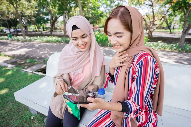 Jeune femme musulmane asiatique en foulard de tête rencontrer des amis et à l'aide de téléphone dans le parc