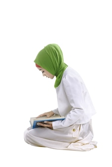 Jeune femme musulmane asiatique lisant le coran