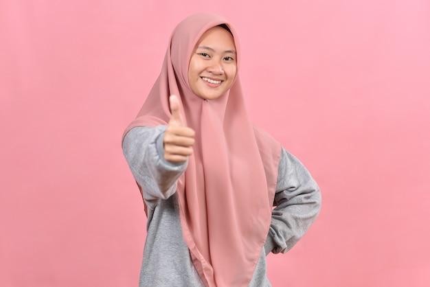 Jeune femme musulmane asiatique montrant le pouce vers le haut sur fond de couleur rose. maquette de l'espace de copie. montrant le pouce vers le haut.