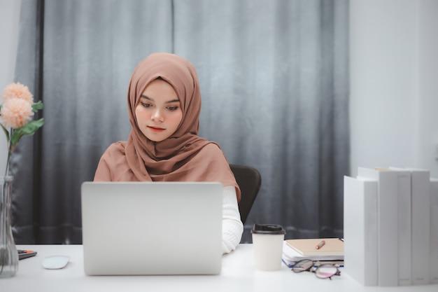 Jeune femme musulmane asiatique en vêtements décontractés intelligents assis et travaillant avec un ordinateur portable à la maison.