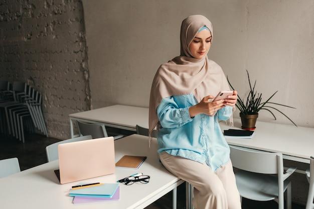 Jeune femme musulmane assez moderne en hijab travaillant dans un bureau, éducation en ligne