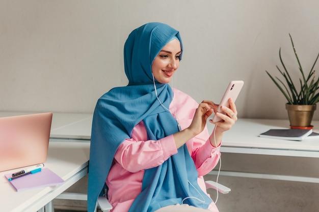 Jeune femme musulmane assez moderne en hijab travaillant sur ordinateur portable dans la salle de bureau, éducation en ligne